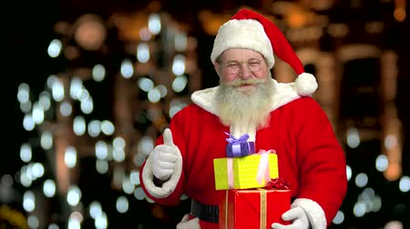 taça : Santa is holding gift boxes. Thumb up gesture, Santa Claus. Stock Footage