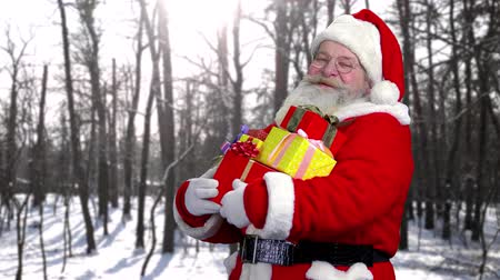 lenda : Santa with presents outdoor. Happy Santa Claus, forest background.