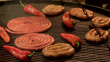 sığır : Sausages and chili peppers, grill. Food being cooked.