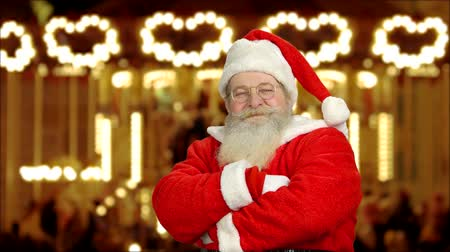 anlaşmak : Santa showing thumbs up. Santa Claus, blurred carousel background. Best Christmas fairs.