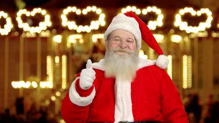 договориться : Santa, thumbs up gesture. Santa Claus on carousel background. Christmas amusement parks worth visiting.