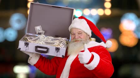 dava : Santa holding suitcase with money. Santa Claus showing thumb up. Christmas and capitalism.