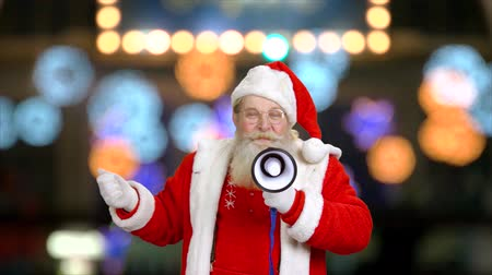 megafon : Santa using a loudspeaker. Santa Claus, bokeh background.