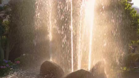 gush : Fountain in slow-mo. Splashes of water and sunlight. Life of nature.
