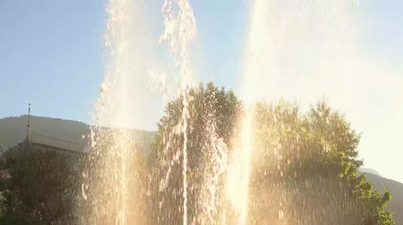 gush : Fountain streams in slow-mo. Water splashes and blue sky.
