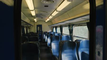 выражать : Inside passenger train wagon. Train seats and windows.