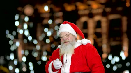 záradék : Santas recommending you to smoke the pipe. Falling lights in the blured background. Stock mozgókép