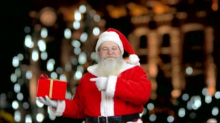 intrigue : Santas promising you a good present for Christmas. Smiling santa. Blured background with falling lights. Stock Footage
