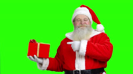 santaclaus : Smiling santas holding the present and pointing at it. Santa with gift in front of green hromakey background.