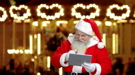 santaclaus : Santa uses the tablet. Modern santa. Blured carousel background. Stock Footage