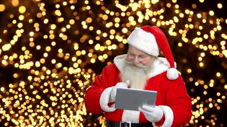 карусель : Santas talking with someone through the gadget. Many bright lights in the background. Стоковые видеозаписи