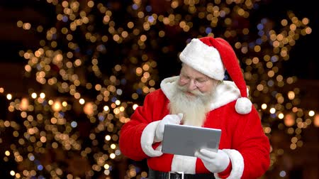 santaclaus : Modern santa is using his tablet to hail someone. Background with darkened lights.