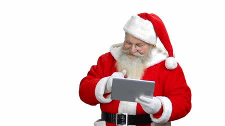 st : Santa is showing his thumb up to the tablet. Santa in the white background.