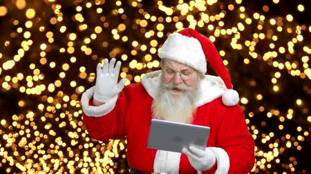 伝える : Santas using the tablet to talk. Background with bright blured lights.