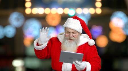 stories : Santa is wishing well by using the tablet. Different blured lights behind.