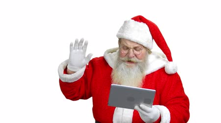 vysvětlení : Santas praising some kid through the tablet. Santa is wishing to keep staying good. Santa with a tablet in the white isolated background.
