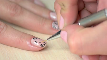 爪 : Beautician doing manicure to young person. Manicurist making fashion design on female nails in beauty salon close up.