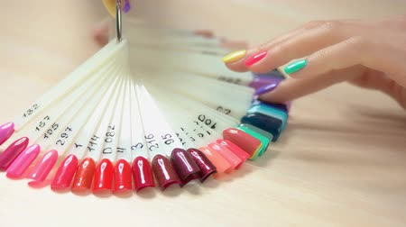 основа : Nail art fashion design samples. Young woman hand with perfect summer manicure choosing nail polish color in nail salon. Artificial nails on transparent basis. Varnish color palette for nails. Стоковые видеозаписи