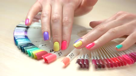 dokonalost : Multicolored manicure and nail polish samples. Young woman well-groomed hands with pastel summer manicure choosing nail color in beauty salon. Skin and nail care concept.