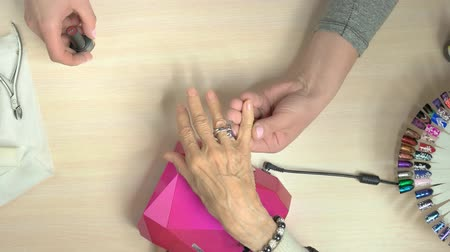 dokonalost : Senior woman receiving manicure in nail salon. Female manicurist doing professional manicure to old woman in beauty salon, top view.