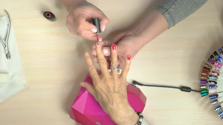 aplikatör : Senior woman receiving manicure in nail salon. Manicure specialist applying red varnish on elderly woman nails in professional nail studio, top view. Stok Video