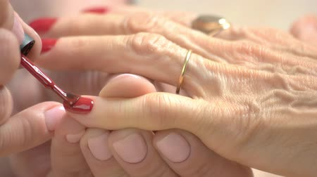 professionally : Manicurist applying red varnish with applicator. Close up process of nail painting with red polish to elderly woman in nail salon.