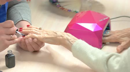 kurutma : Elderly woman is getting manicure in nail salon. Nail cosmetician doing manicure to senior woman in professional nail studio.