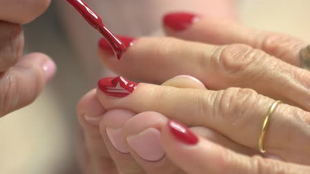 lakier do paznokci : Close up nail painting with red lacquer. Manicurist is covering nails to woman by red varnish. Master class of professional manicure in nail salon.