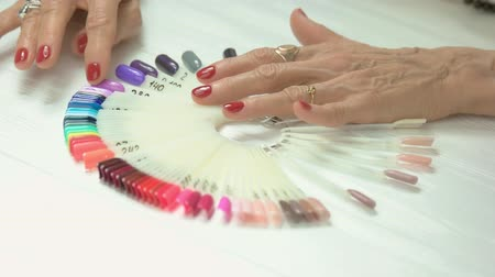 küfelik : Luxury female hands with red manicure. Senior woman wrinkled hands with red nails choosing nail color on samples. Elderly woman in nail salon.