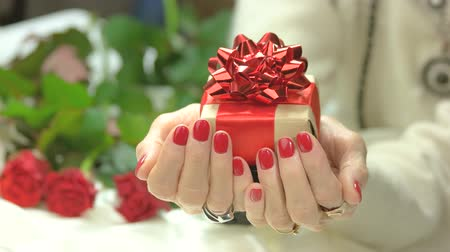 presentes : Female manicured hands with gift box. Handmade gift box with red box in senior woman manicured hands. Birthday celebration concept. Stock Footage