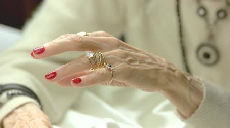 bilge : Elderly woman putting on golden rings. Senior woman hands with perfect red manicure wearing luxury jewelry. Aristocratism and elegance concept. Stok Video