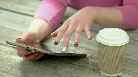 латте : Manicured hands using computer tablet. Young woman hands with modern manicure holding pc tablet. Cardboard cup of coffee on old wooden table. Стоковые видеозаписи