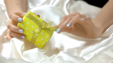 womanhood : Gentle winter manicure and gift box. Young woman well-groomed hands is unpacking yellow dotted box with gift. Holidays and celebrations concept.