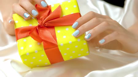 womanhood : Gift box in female manicured hands. Young woman hands with winter design manicure holding yellow gift box with red ribbon. Christmas and New Year holidays concept.