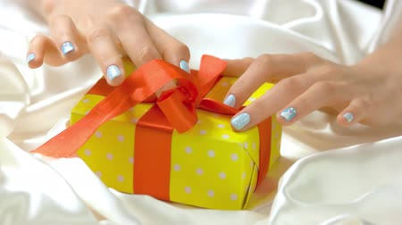 womanhood : Manicured hands untied ribbon on gift box. Beautiful female hands with perfect winter manicure unpacking yellow gift box on white silk. Holidays and celebrations concept.