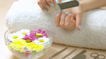 chryzantema : Woman filing nails in spa salon. Female hands with nails file, glass bowl with water and chrysanthemums, manicure equipment. Beauty and spa salon.