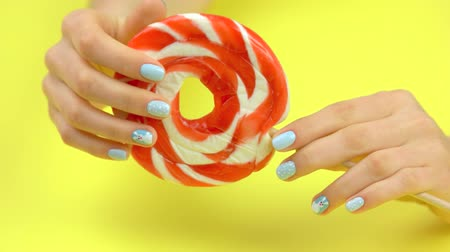 manikür : Large colored lollipop moving in female hands. Delicious spiral lollipop with stick in woman hands. Female hands with winter design manicure on yellow background. Stok Video