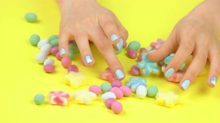 dokonalost : Well-groomed hands with winter manicure. Woman hands with beautiful winter manicure placing multicolored sweet candies on yellow background.