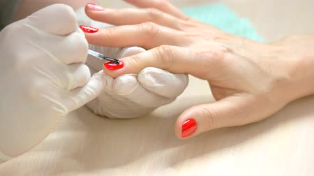 professionalism : Specialist covers the nail of client by fixer. Nail master fixing red polished index finger nail by transparent fixer in beauty salon close up. Stock Footage