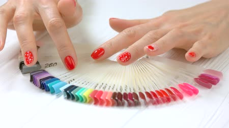 desenli : Hands with beautiful nail design. Well-groomed hands of young woman and nail color samples in beauty salon close up.