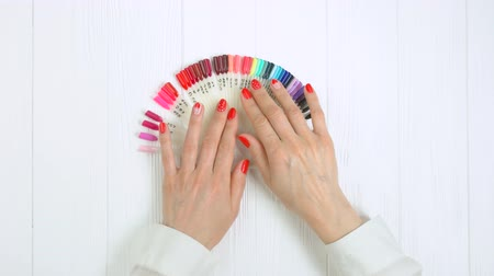 artificial color : Hands and nail color samples, top view. Red manicure with romantic design and nail colors palette on table in beauty salon.