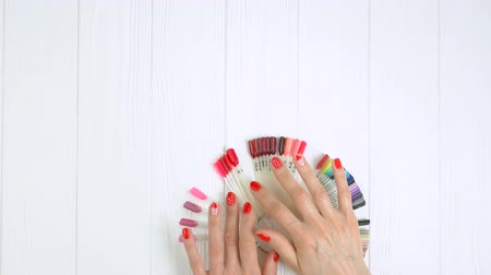 desenli : Manicured hands and nail color palette. Young woman hands with red patterned manicure choosing nail color on an artificial nail samples, top view. Stok Video