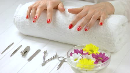 chrysanthemum : Hands with fresh manicure in spa salon. Well-groomed hands knocking on white towel with fingers. Manicure intrument, bowl with water and flowers. Spa treatment for hands. Stock Footage