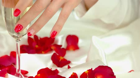 sensualita : Glass of champagne in hands, red petals. Close up well-groomed hands with beautiful manicure and glass of sparkling beverage, red rose petals on white silk. Filmati Stock