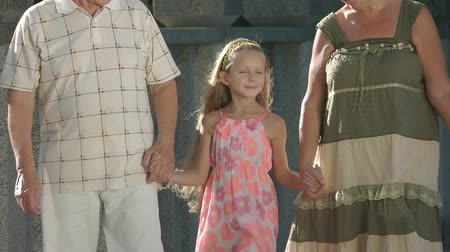孫娘 : Girl walking with her grandparents. Child holding hands of grandparents in beautiful summer day, slow motion. Happy little girl.