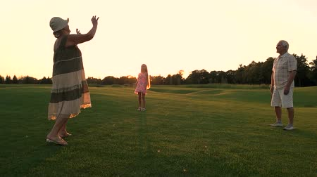 孫娘 : Seniors with granddaughter on green meadow. Slow motion grandparents with their grandchild playing sport game with ball on fresh air, summer sunset. Happy family weekend and relax.