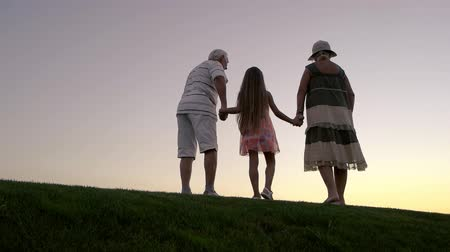бабушка или дедушка : Girl with grandparents at sunset. Slow motion senior man and woman with granddaughter on evening sky background. Enjoying the infinity.