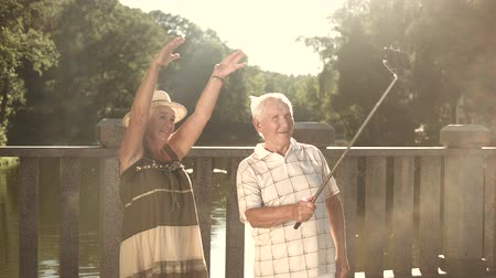 emeryt : Seniors taking a video with selfie stick. Cheerful couple of elderly people posing and smiling, holding monopod on beautiful nature background.