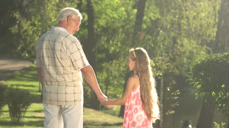 personalidade : Grandfather talking to his granddaughter in the park. Old man giving an advice to his grandchild walking in the park. Cultivation a personality by senior generation.