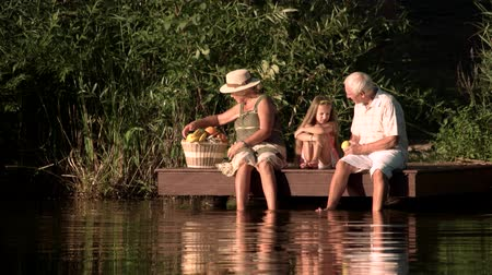 孫娘 : Old people and grandchild with picnic basket. Grandparents and granddaughter sitting near water with basket full of fruits. Upset girl at lake.
